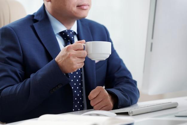 Bebouwde zakenman die koffie hebben bij zijn bureau die het scherm van computer bekijken Gratis Foto