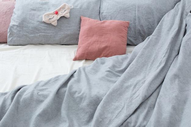 Bed met grijs linnen en slaapmasker Premium Foto