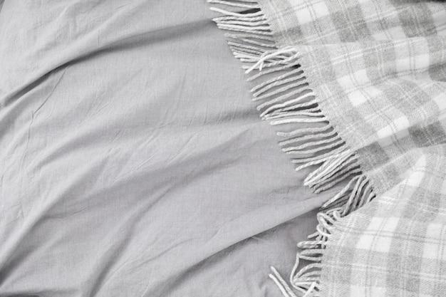 Bed met grijze wollen plaid of quilt en grijs beddengoed. Premium Foto