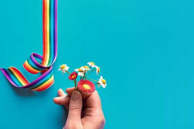 Bedankt dokters en verpleegsters! regenbooglint op turqiouse achtergrond. vrouw hand met kamille en sleutelbloemen, eenvoudige dank u symbolen. Premium Foto