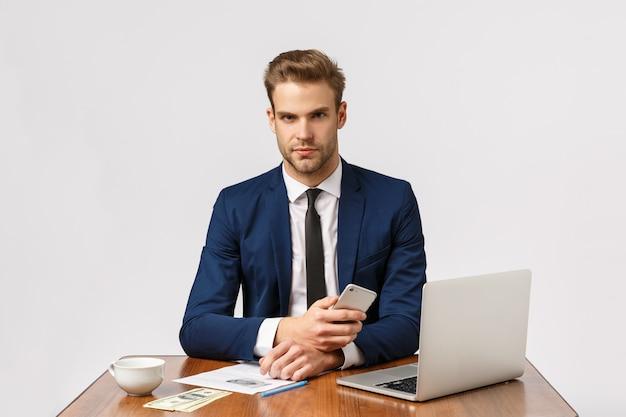 Bedrijf, bedrijf, bedrijfsconcept. ernstige baas zit in zijn kantoor met een gefocust, fronsend gezicht, houdt een smartphone vast, wacht een belangrijk gesprek, heeft veel geld op het spel Premium Foto
