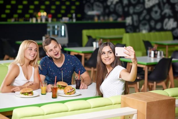 Bedrijf dat telefoon bekijkt en selfie in koffie neemt Premium Foto