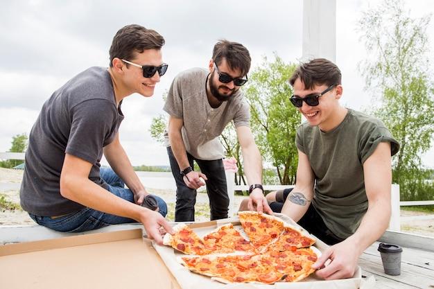 Bedrijf van lachende vrienden die pizza op picknick eten Gratis Foto
