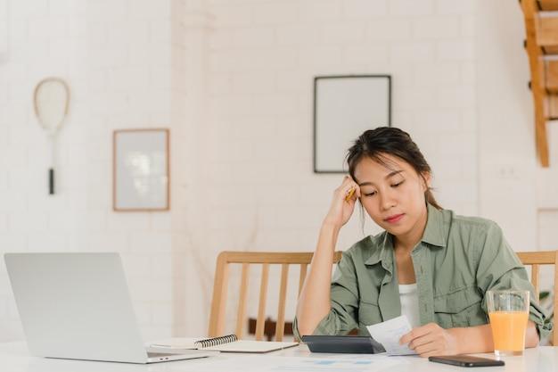 Bedrijfs aziatische vrouwenverslagen van inkomsten en uitgaven thuis Gratis Foto