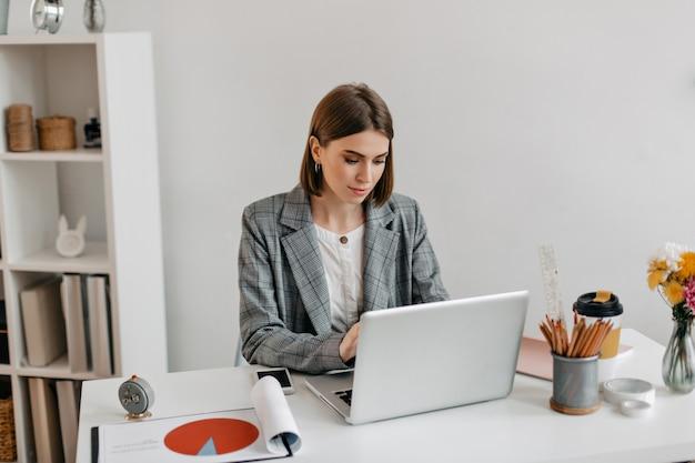 Bedrijfs dame in grijs jasje dat in laptop werkt. portret van een vrouw in kantoor. Gratis Foto