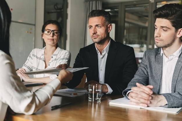 Bedrijfs-, loopbaan- en plaatsingsconcept - raad van bestuur zittend aan tafel in kantoor, en onderzoek van cv van vrouwelijke werknemer tijdens vergadering Premium Foto