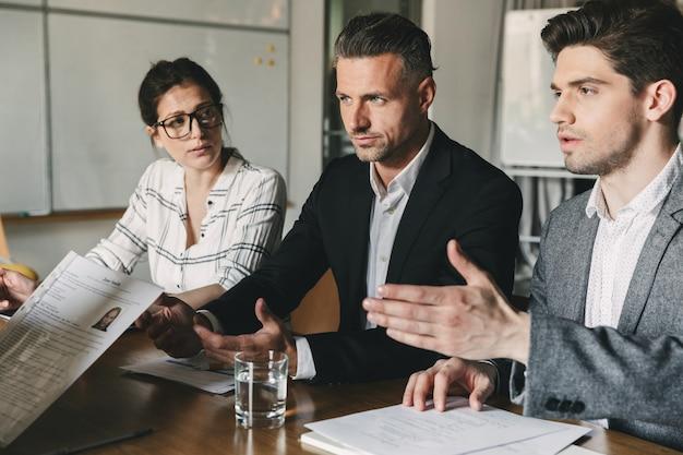 Bedrijfs-, loopbaan- en plaatsingsconcept - raad van bestuur zittend aan tafel in kantoor, en onderzoek van cv van vrouwelijke werknemer tijdens zakelijke bijeenkomst Premium Foto