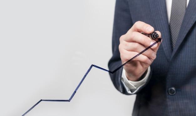 Bedrijfs mens die een lijn van de de groeigrafiek maakt Gratis Foto