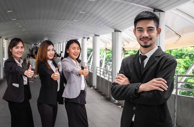 Bedrijfs mens die een succesvolle collectieve groep met omhoog duimen leidt Premium Foto