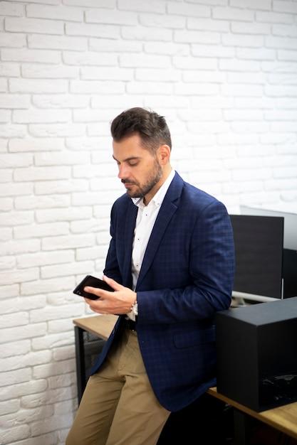 Bedrijfs mens die telefoon bekijkt Gratis Foto