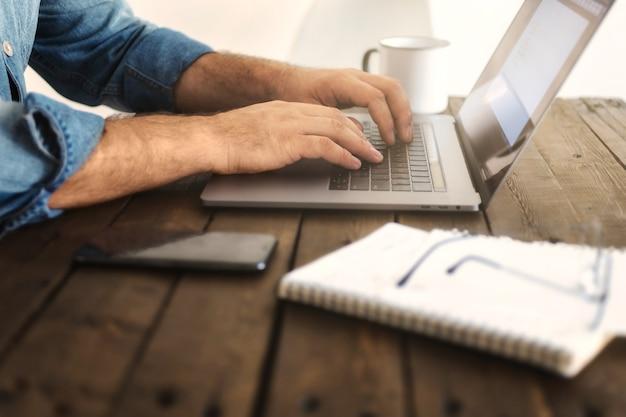 Bedrijfs mens die thuis met laptop werkt. man hand te typen op een computer. remote werk of onderwijs concept Premium Foto