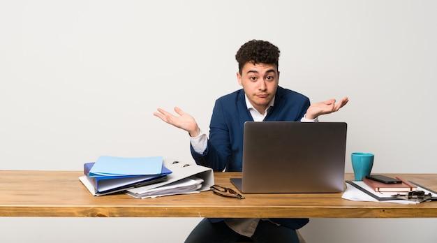 Bedrijfs mens in een bureau dat twijfels heeft terwijl het opheffen van handen Premium Foto
