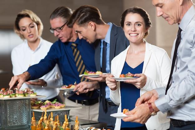 Bedrijfs mensen die snacks van buffet table Gratis Foto