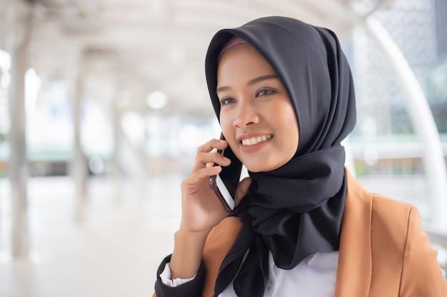 Bedrijfs moslimvrouw die telefoon in stad met behulp van. Premium Foto
