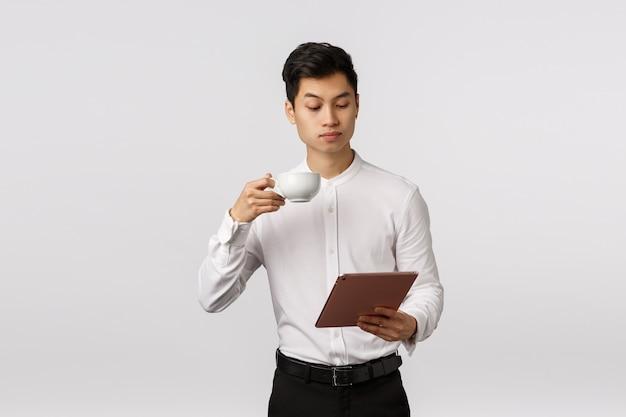 Bedrijfs-, technologie- en financieringsconcept. serieus uitziende elegante en stijlvolle, succesvolle mannelijke ondernemer lezen van nieuws in digitale tablet, koffie drinken uit de beker, documenten online bestuderen Premium Foto