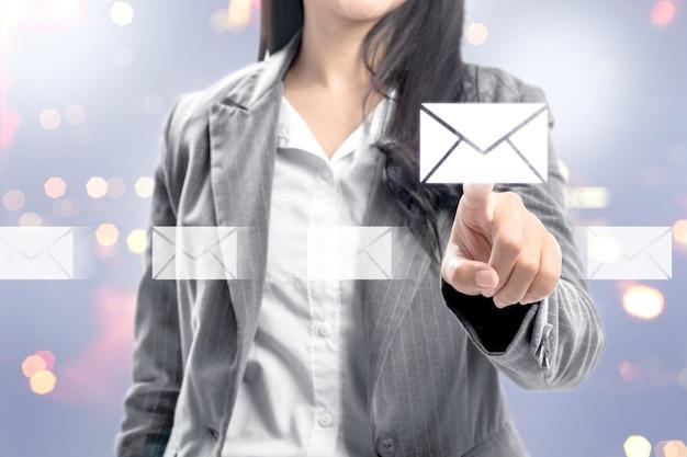 Bedrijfs vrouw die e-mailpictogrammen op het virtuele scherm richt Premium Foto
