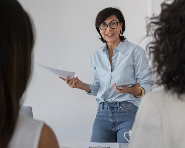 Bedrijfs vrouw die iets verklaart aan haar collega's Gratis Foto
