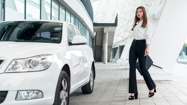 Bedrijfs vrouw die naar de auto gaat Gratis Foto