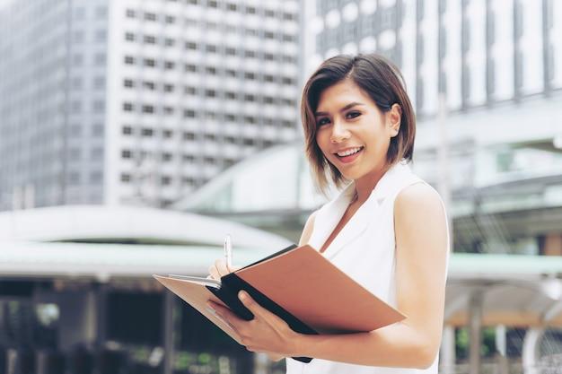 Bedrijfs vrouw die op boek schrijft Gratis Foto