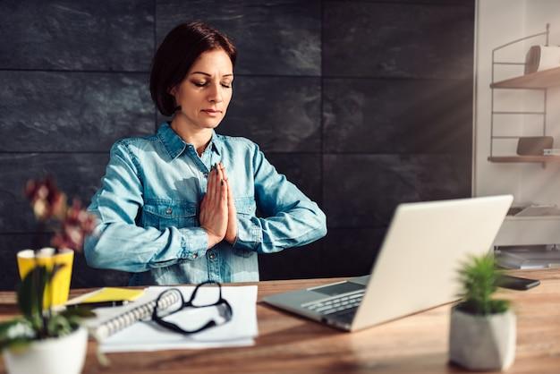 Bedrijfs vrouw die op het werk mediteert Premium Foto