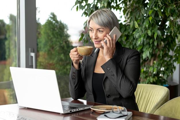 Bedrijfs vrouw in onderbreking die over telefoon spreekt Gratis Foto