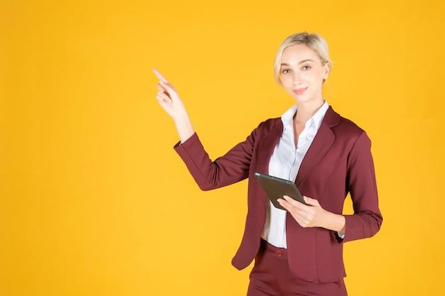 Bedrijfs vrouw richt iets op gele achtergrond Premium Foto