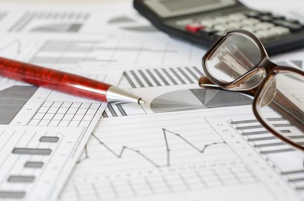 Bedrijfsanalyse, grafieken en diagrammen. pen, bril, rekenmachine. Premium Foto
