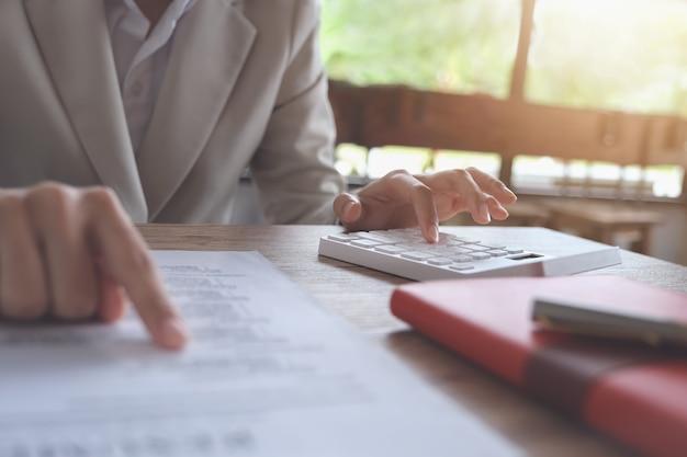 Bedrijfsboekhoudingsconcept, bedrijfsmens die calculator gebruiken aan het berekenen van begroting en leningsdocument in bureau. Premium Foto