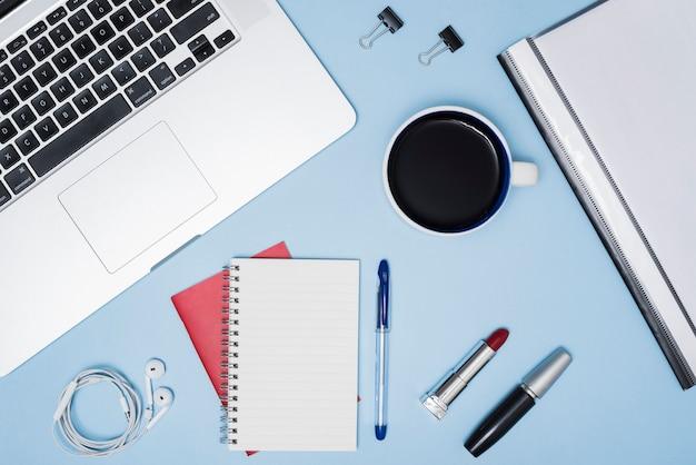 Bedrijfsbureau met make-upobjecten; koffiekop; bestanden en oortelefoon over blauwe achtergrond Gratis Foto
