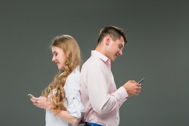 Bedrijfsconcept. de twee jonge collega's met mobiele telefoons op grijze achtergrond Gratis Foto