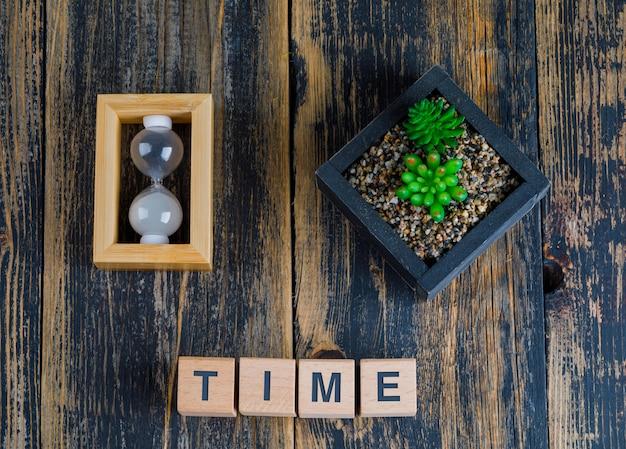 Bedrijfsconcept met tijdwoord op houten kubussen, zandloper en installatie Gratis Foto