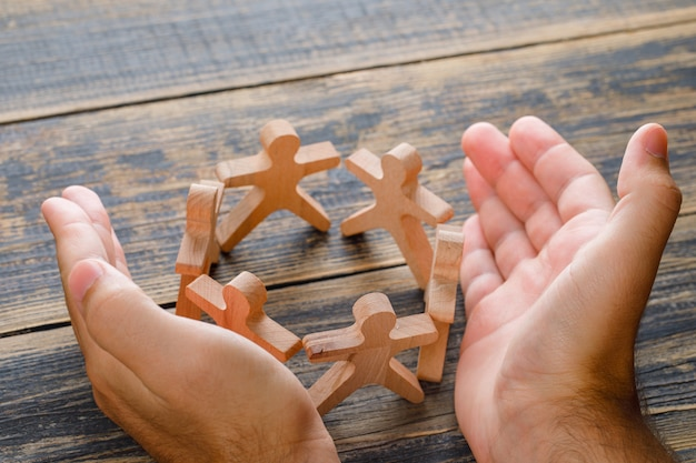Bedrijfsconcept succes op houten tafelblad bekijken. handen beschermen houten figuren van mensen. Gratis Foto