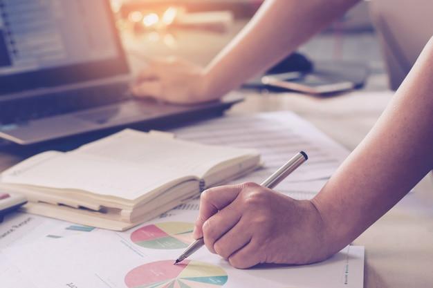 Bedrijfsconcept: vrouwenhand die laptop met behulp van en pen houdt en buslijn richtend grafiek Premium Foto