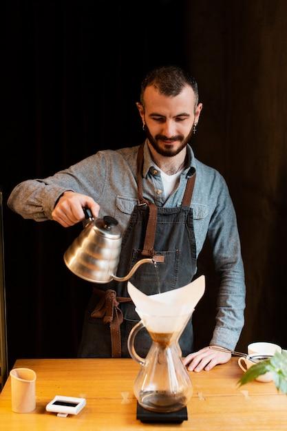 Bedrijfseigenaar die in koffiewinkel werken Gratis Foto