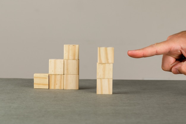 Bedrijfsgroei concept op grijs en wit muur zijaanzicht. man met houten blokken toren. Gratis Foto