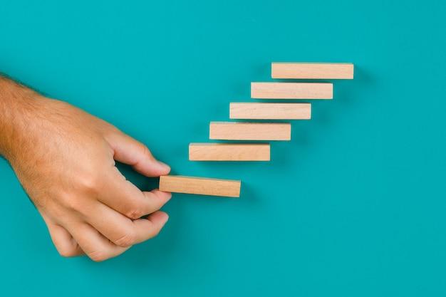 Bedrijfsgroei concept op turquoise tabel plat lag. hand houten blokken stapelen. Gratis Foto