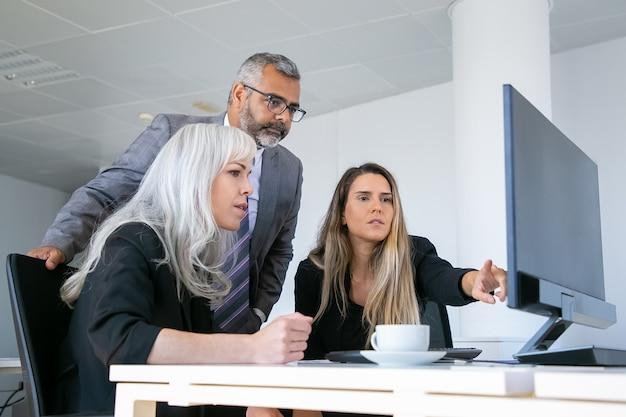 Bedrijfsgroep presentatie op pc-monitor kijken en project bespreken, zittend op de werkplek met kopje koffie en wijzend op display. zakelijke communicatie concept Gratis Foto
