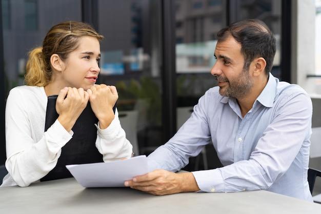 Bedrijfsleider en zijn vrouwelijke assistent die taken bespreken Gratis Foto