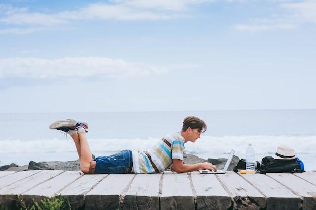 Bedrijfsmens die aan het strand met laptop werken Premium Foto