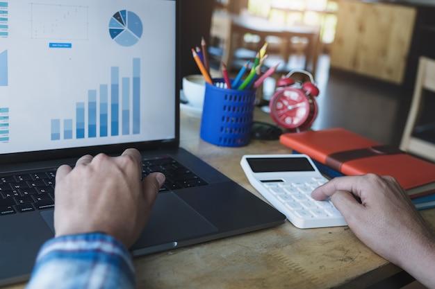 Bedrijfsmens die calculator gebruiken om balans jaarlijks met holdingspen te herzien en laptop computer met behulp van Premium Foto