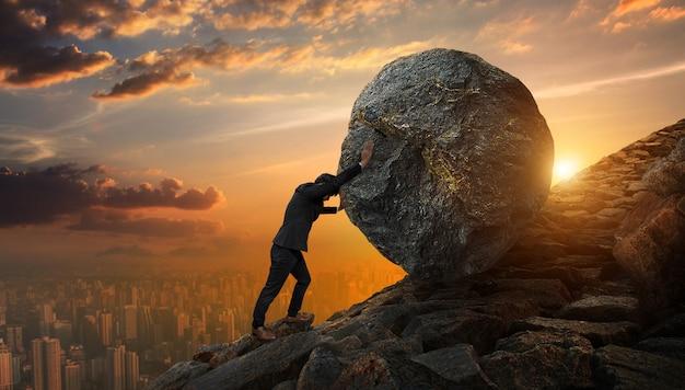 Bedrijfsmens die grote steen tot heuvel, bedrijfs zwaar taken en problemenconcept duwen. Premium Foto