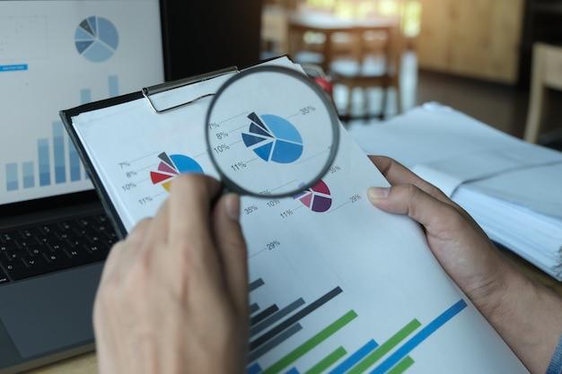Bedrijfsmens die het overdrijven gebruiken om balans jaarlijks met het gebruiken van laptop computer te herzien Premium Foto