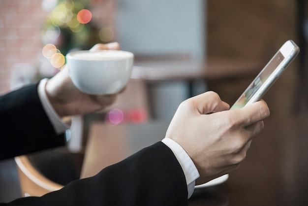 Bedrijfsmens die mobiele telefoon met behulp van terwijl het drinken van koffie in koffiewinkel Gratis Foto