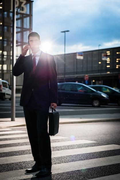Bedrijfsmens die telefoon in avond in openlucht met behulp van Premium Foto
