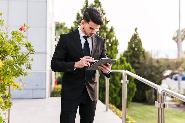 Bedrijfsmens die zijn tablet gebruiken Gratis Foto