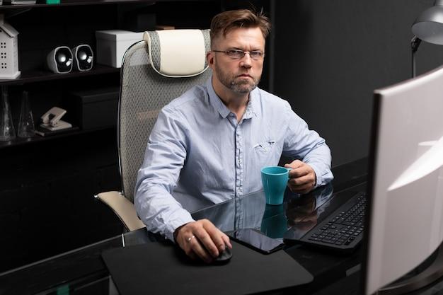 Bedrijfsmens met glazen die in het bureau bij computerlijst werken en koffie van heldere kop drinken Premium Foto