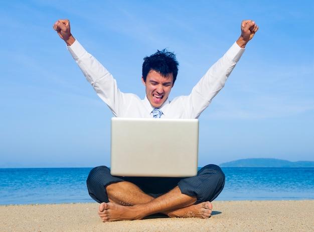 Bedrijfsmens op strand met laptop Gratis Foto