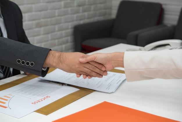 Bedrijfsmensen die handen boven bureau schudden. Premium Foto