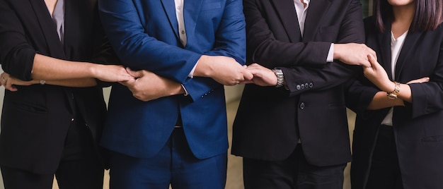 Bedrijfsmensen die handen samen in lijn ontmoeten. jonge mensen uit het bedrijfsleven zijn hand in hand. Premium Foto