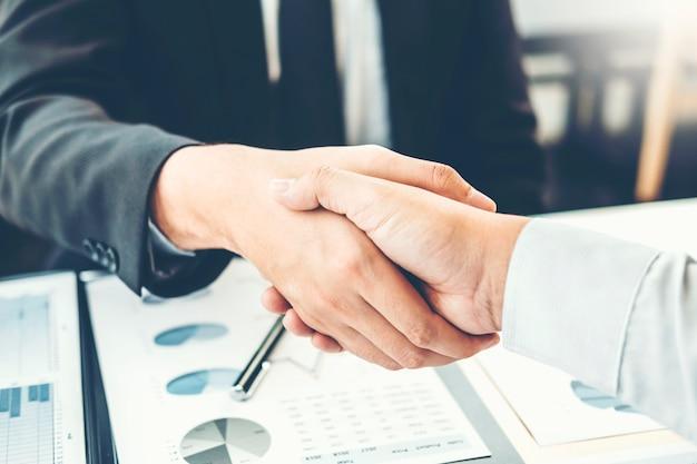 Bedrijfsmensencollega's die handen schudden die het concept van de planningsstrategieanalyse ontmoeten Premium Foto
